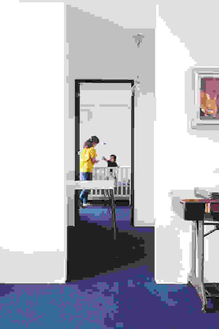 リビングから見て奥が寝室。手前はワークスペースで白いデスクを置いた 株式会社ブルースタジオ モダンデザインの リビング