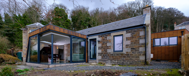 The rear extension to Woodend Cottage is clad in Corten steel and features large glass sliding doors Modern houses by Woodside Parker Kirk Architects Modern Iron/Steel