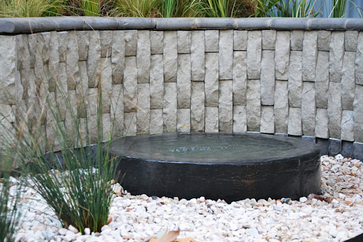 Water feature and bog garden Industrial style gardens by Acton Gardens Industrial Concrete