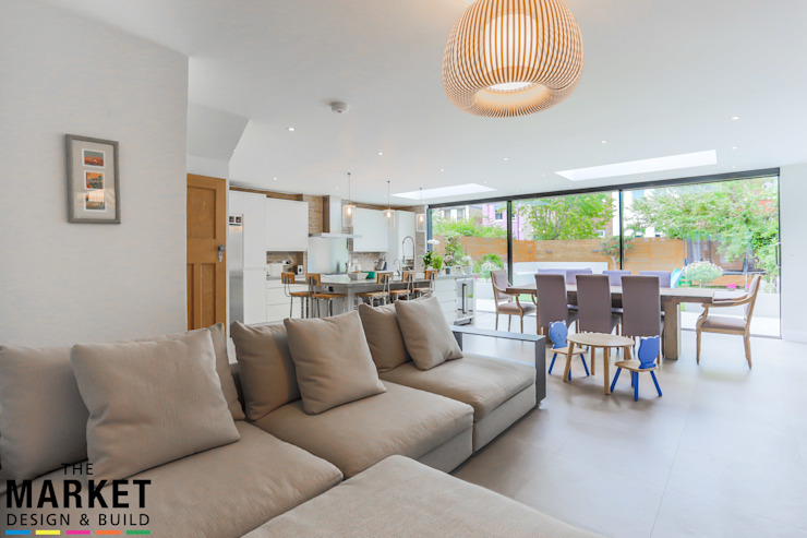 STUNNING NORTH LONDON HOME EXTENSION AND LOFT CONVERSION:  Living room by The Market Design & Build,