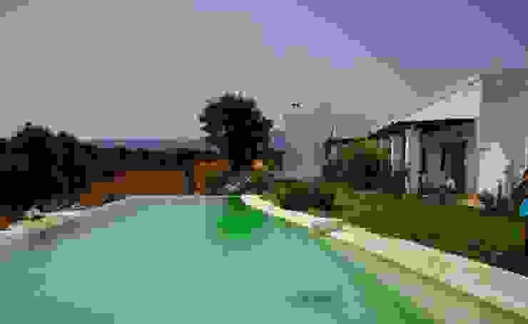 il rapporto tra campagna abitazione tradizionale e piscina è un perfetto equilibrio di tutti gli elementi in gioco Piscina in stile mediterraneo di Natura&Architettura Mediterraneo