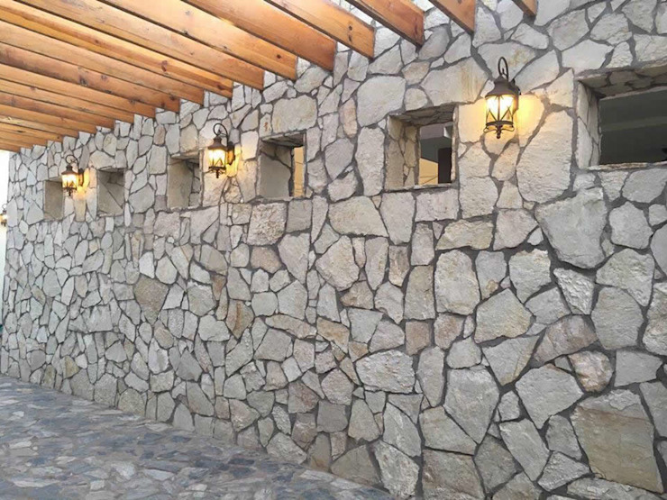 MURO DE PIEDRA LAJA EN CORREDOR PRINCIPAL Paredes y pisos de estilo rural de homify Rural Piedra