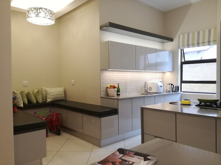 high gloss grey doors with grey counter tops and charcoal grey mat by Première Interior Designs Modern
