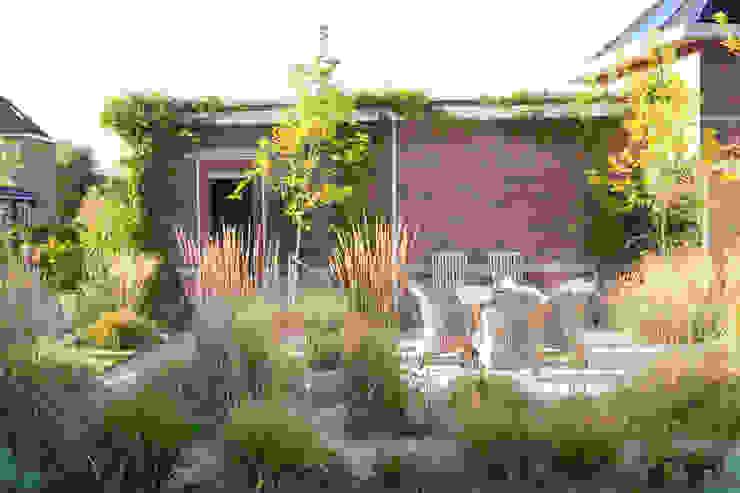 Sfeervolle tuin met gazon en siergras van Dutch Quality Gardens, Mocking Hoveniers