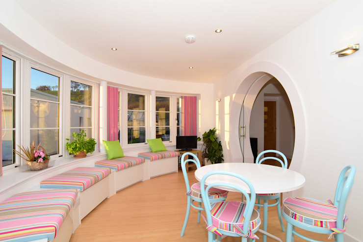 The curved Dayroom with matching cushions and blinds in the seaside theme. Jardines de invierno eclécticos de Roundhouse Architecture Ltd Ecléctico Vidrio