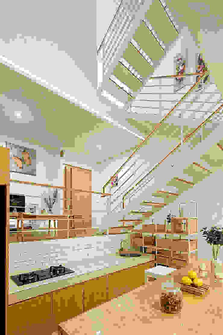 Phòng bếp và bàn ăn được bố trí ở ngay cạnh cầu thang. bởi Công ty TNHH TK XD Song Phát Châu Á Đồng / Đồng / Đồng thau