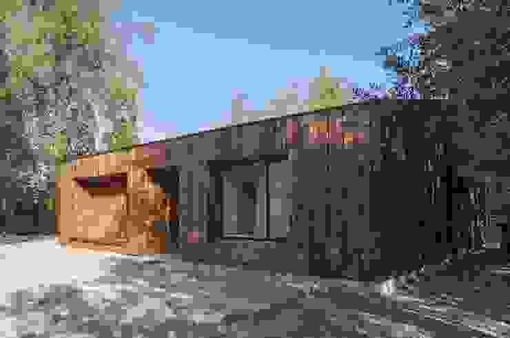 Casa envuelta en madera de Crescente Böhme Arquitectos Rústico Piedra