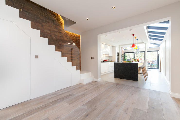 Minimalist hallway with white staircase leading through to open-plan kitchen Timothy James Interiors Escaleras