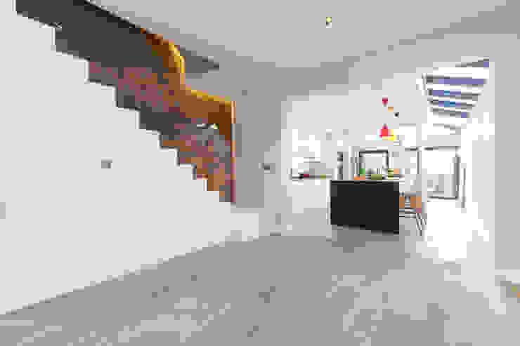 Minimalist hallway with white staircase leading through to open-plan kitchen Timothy James Interiors Stairs