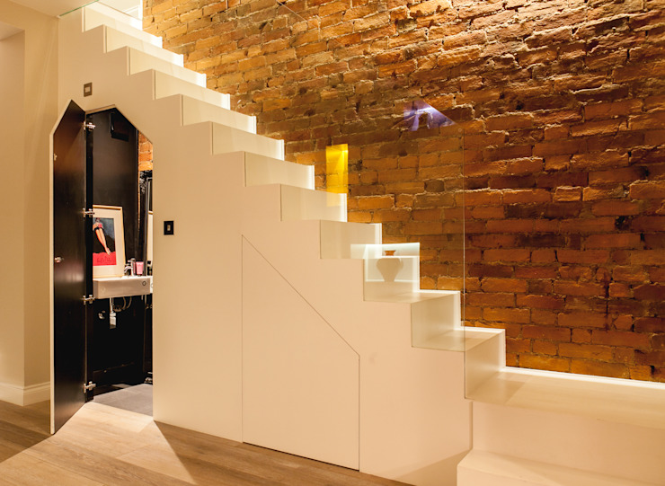 Minimalist white staircase with exposed brick wall and concealed cloakroom Timothy James Interiors Escaleras