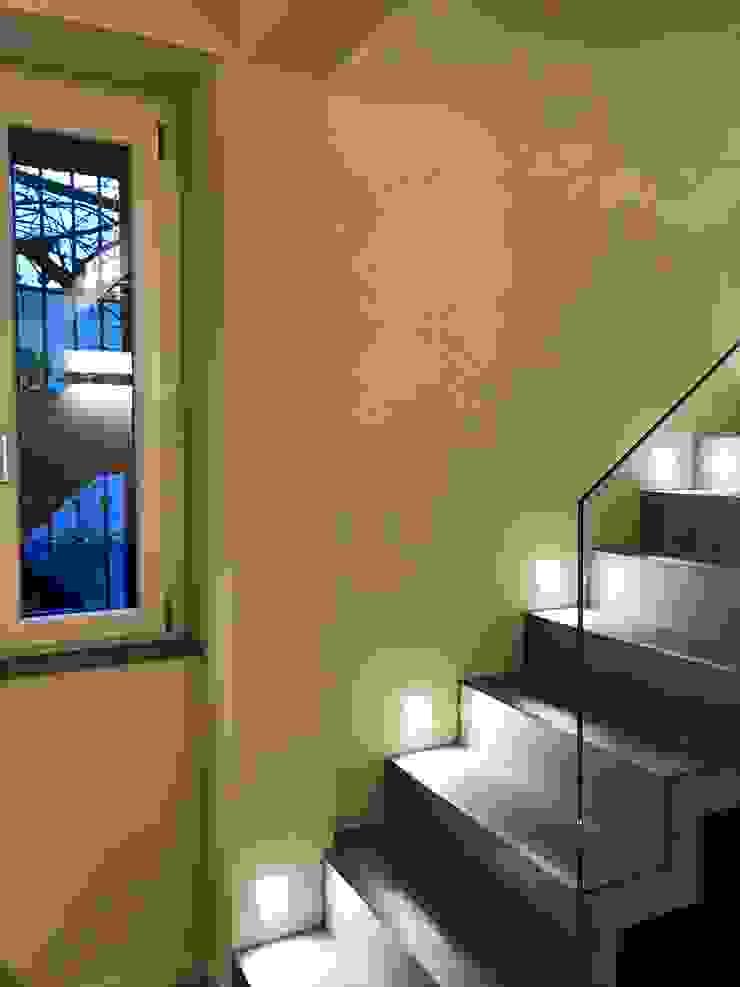 Scala in muratura rivestita in microcemento con illuminazione a parete di Cozzi Arch. Mauro Moderno