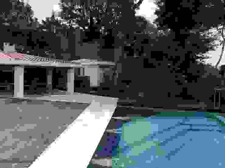 Primer plano de la piscina y al fondo el sector parrillera OMAR SEIJAS, ARQUITECTO Piscinas de estilo moderno