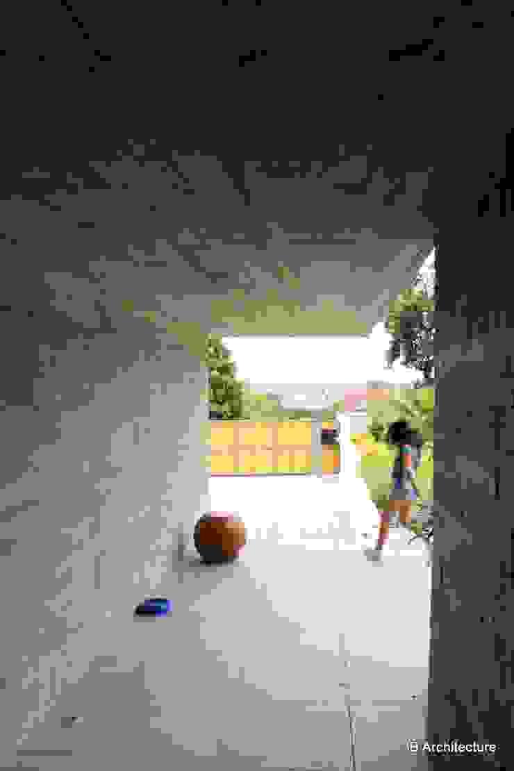 L'entrée se fait à couvert sous un port-à-faux en béton Murs & Sols minimalistes par 3B Architecture Minimaliste Béton