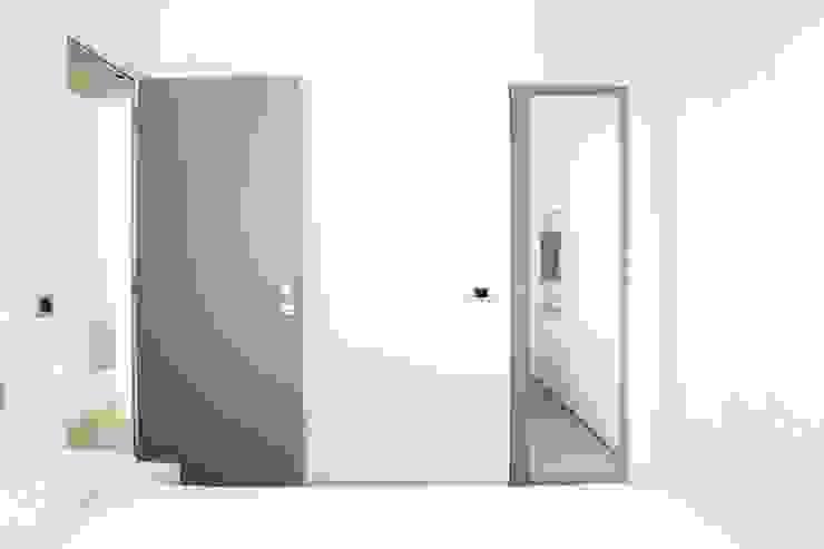 Camera da letto matrimoniale con porta a specchio per accesso al bagno Francesco Ruffa Architetto Camera da letto moderna