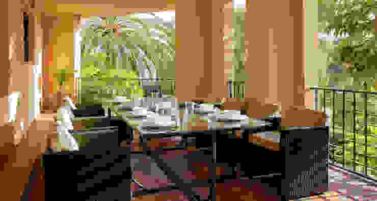 Terraza decorada con un juego de mesa y sillas de mimbre Comedores de estilo tropical de AVANTUM Tropical