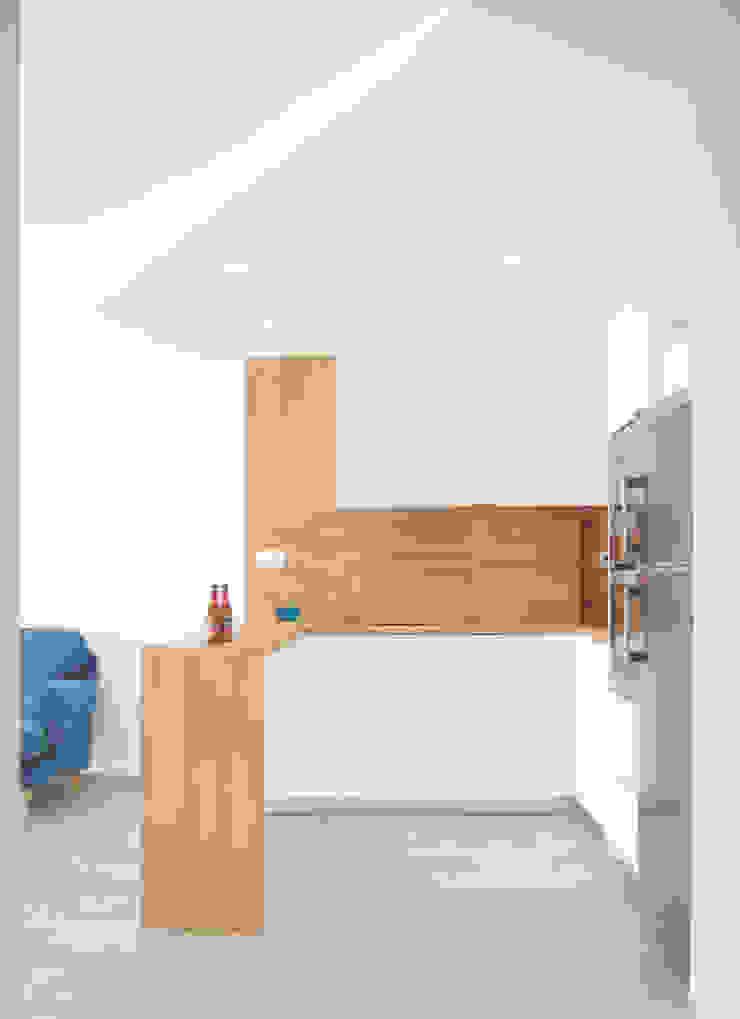 Cocina en L fabricada con encimara de madera y muebles en blanco de Loft 26 Moderno Madera Acabado en madera