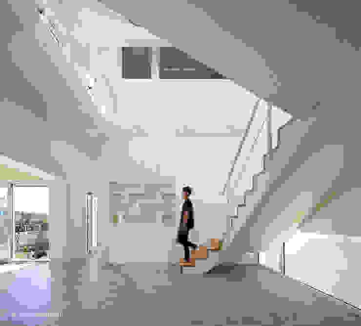 1층 계단실과 상부 보이드 공간 모던스타일 거실 by 건축사사무소 모뉴멘타 모던