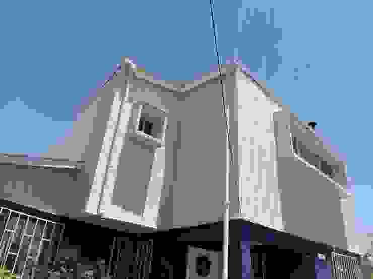 Vista desde antejardín a esquina nor-oriente_ Foto vivienda construida de BIM Urbano Minimalista Aluminio/Cinc