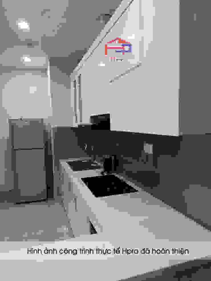 Tủ bếp acrylic màu trắng nhà chị Hiền có bề mặt mịn, phẳng và sáng bóng như gương.: hiện đại  by Nội thất Hpro, Hiện đại