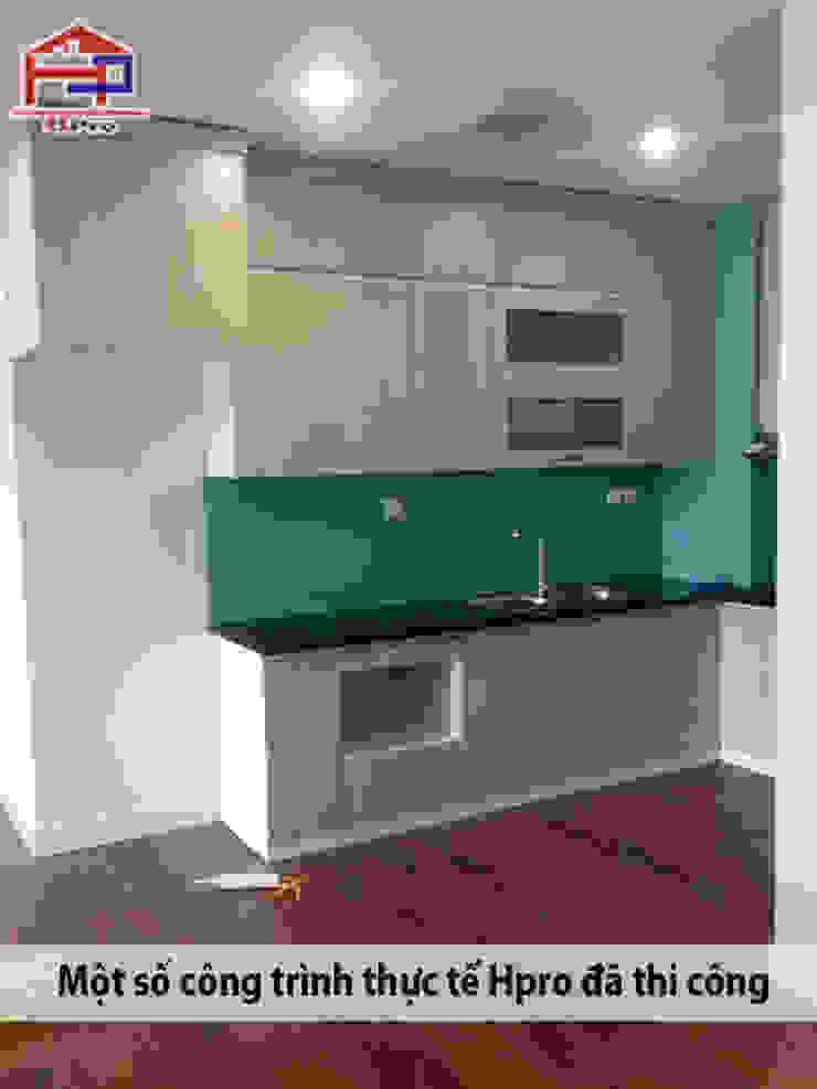 Tủ bếp laminate màu vân gỗ với bề mặt phẳng, mịn và bóng tạo cho không gian nét độc đáo riêng: hiện đại  by Nội thất Hpro, Hiện đại