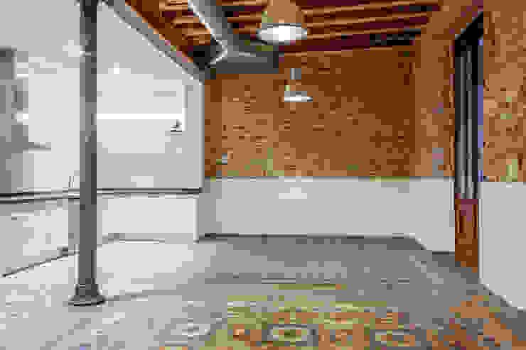 Salón con pavimento hidraulico y paredes de obra vista originales Salones de estilo industrial de Xmas Arquitectura e Interiorismo para reformas y nueva construcción en Barcelona Industrial Ladrillos