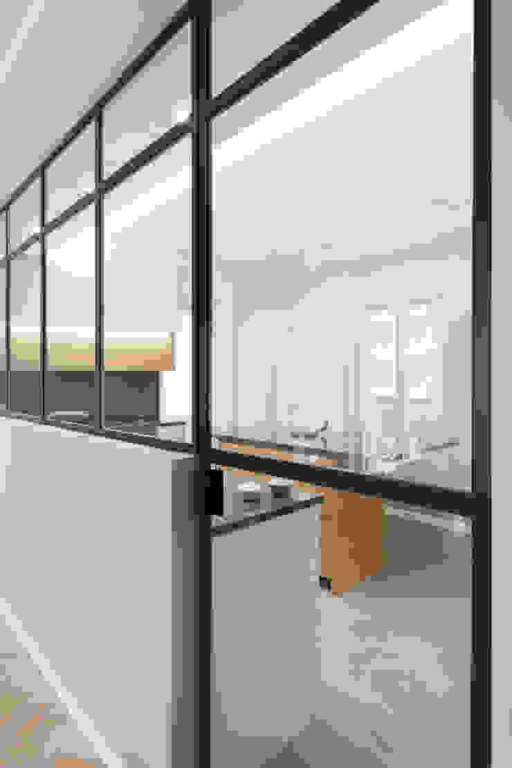 Porta e vetro integrata in vetrata verso la cucina di PLUS ULTRA studio Minimalista Ferro / Acciaio