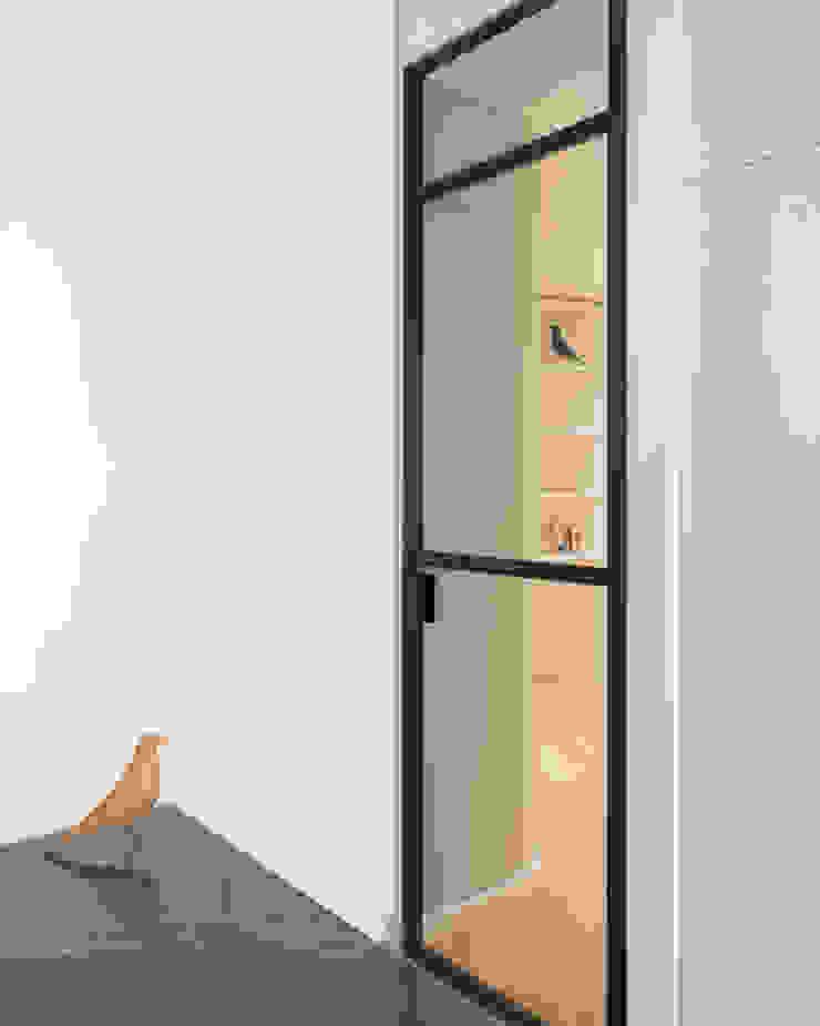 Porta a vetri della cucina verso ingresso di PLUS ULTRA studio Minimalista Ferro / Acciaio