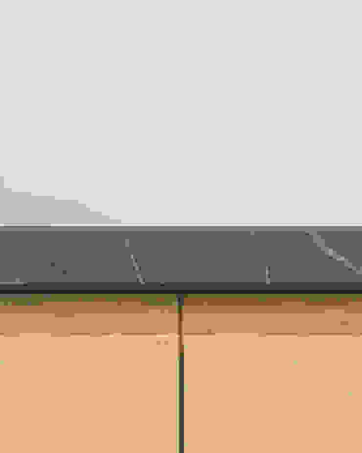 Dettaglio isola in rovere e piano cucina in marmo grigio di PLUS ULTRA studio Minimalista Marmo