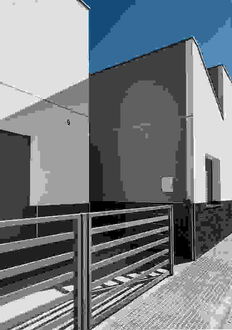 Espacio de entrada de Casa Moderna de una planta. OOIIO Arquitectura Jardines delanteros Aglomerado Gris