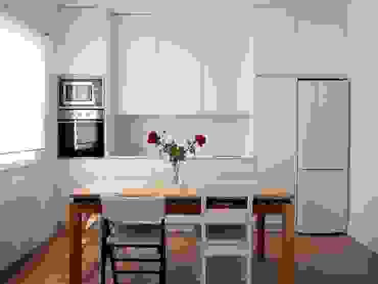 Cocina blanca integrada en salón Comedores de estilo moderno de Reformmia Moderno