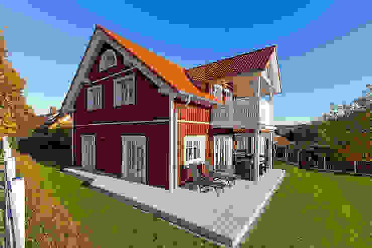 """Ökohaus """"Vättern"""" mit roter Holzfassade und Terrasse:  Balkon von Skan-Hus Projekt GmbH"""