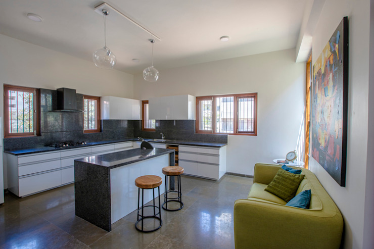 Kitchen with island wrapped around the internal courtyard Kamat & Rozario Architecture Modern kitchen