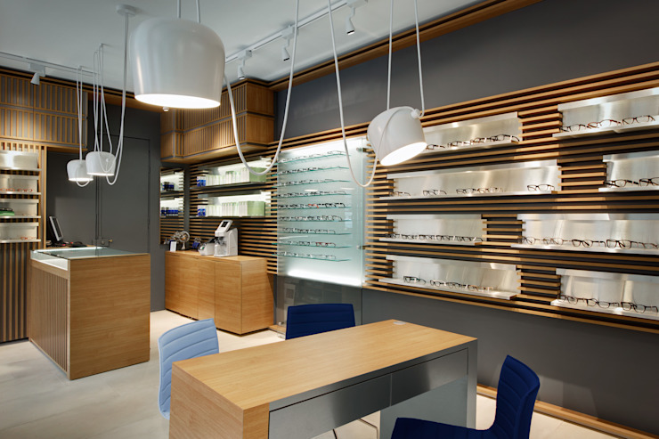 "Magasin d'optique design ""Thomas Opticien"", dans le 5ème arrondissement à Paris. Vue de la table de vente assis. Locaux commerciaux & Magasin modernes par Alessandra Pisi / Pisi Design Architectes Moderne Bois Effet bois"