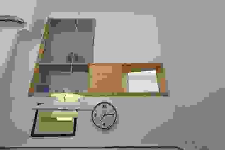 """Cucina - zona pranzo con la """"finestra"""" comunicante con l'ingresso e la stanza studio adiacente di Daniele Arcomano Moderno"""