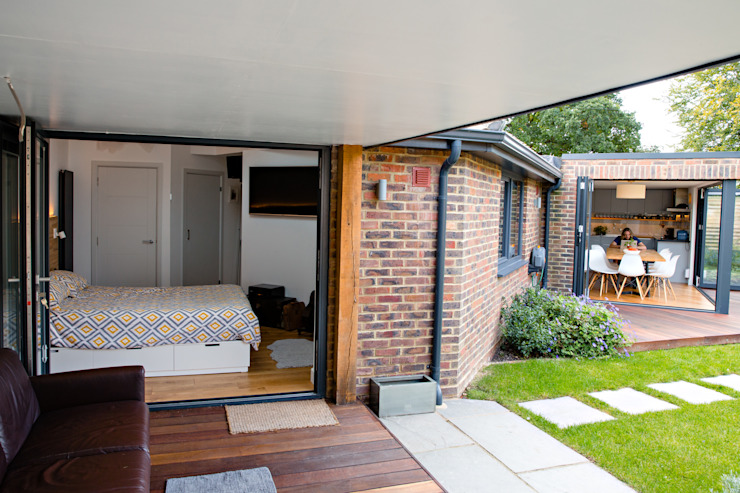View of covered outdoor seating area, master bedroom and bi-folding doors Modern Evler dwell design Modern