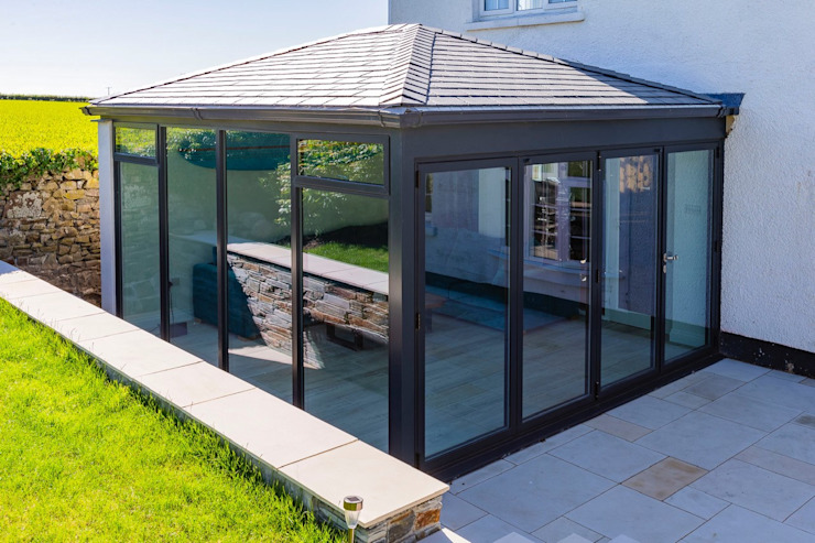 A warm roof and aluminium extension carried out in Bude. モダンスタイルの 温室 の Bude Windows & Conservatories Ltd モダン アルミニウム/亜鉛