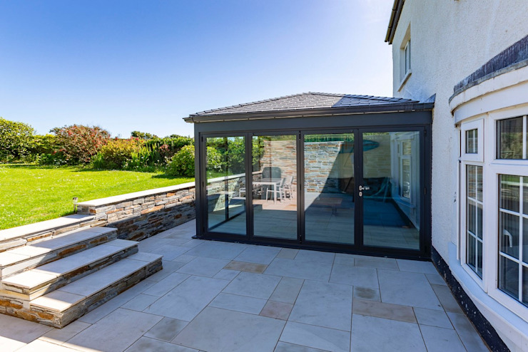 A warm roof and aluminium extension carried out in Bude. モダンスタイルの 温室 の Bude Windows & Conservatories Ltd モダン