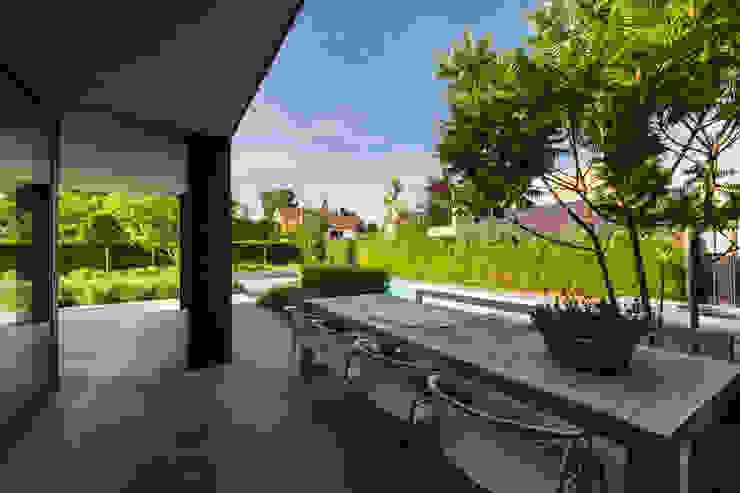 Betonvloer onder overkapping Moderne balkons, veranda's en terrassen van Buro Buitenom exterieurontwerpers Modern