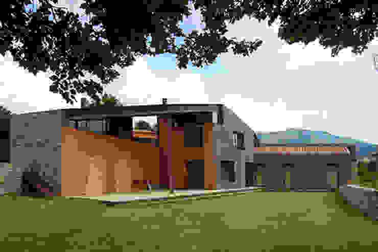 Vista de la fachada principal y jardín según el modelo de la arquitectura vernácula del lugar.: Casas unifamilares de estilo  de SANTI VIVES ARQUITECTURA EN BARCELONA, Moderno