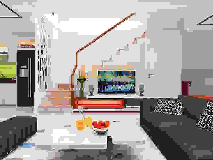 Phòng khách nhà ống hiện đại nổi bật nhờ cách lựa chọn màu sắc khôn khéo bởi Công Ty Thiết Kế Xây Dựng LOUIS