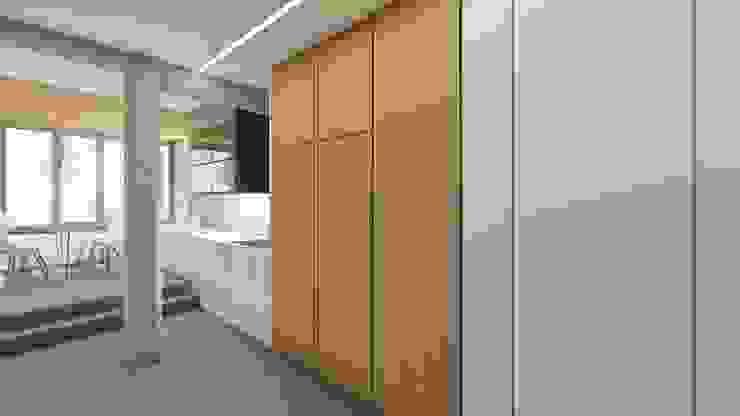Entrada a la vivienda. Cocina integrada en armarios de madera y encimera blanca. de Barreres del Mundo Architects. Arquitectos e interioristas en Valencia. Moderno Madera maciza Multicolor