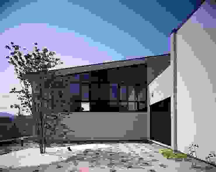 カーテンウォールのサッシが印象的な中庭 モダンな庭 の イクスデザイン / iks design モダン タイル