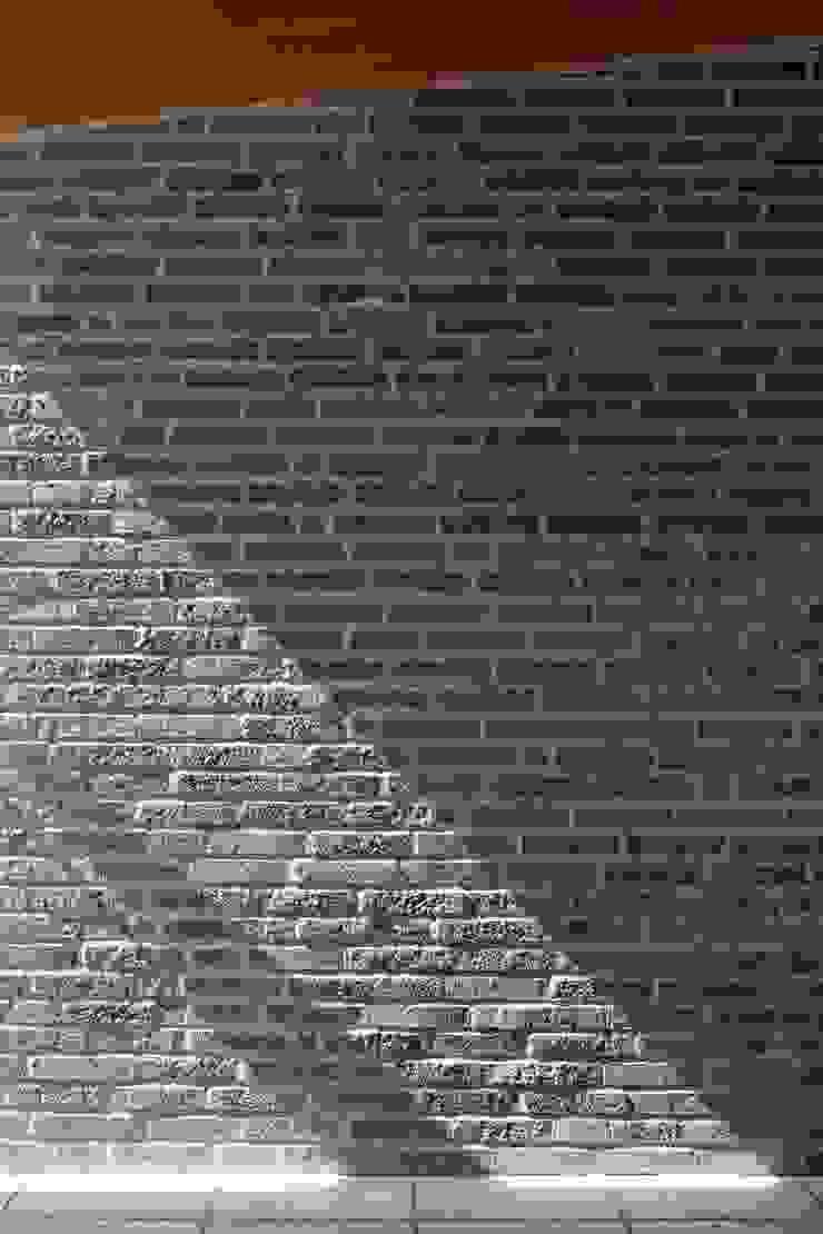 日差しがタイルの質感を強調するエントランスホール モダンな 壁&床 の イクスデザイン / iks design モダン タイル