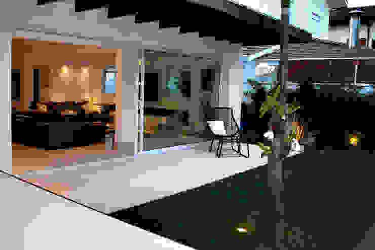 """Varanda em """"L"""" com cobertura em madeira suspensa por RAWI Arquitetura + Design Minimalista Madeira Efeito de madeira"""