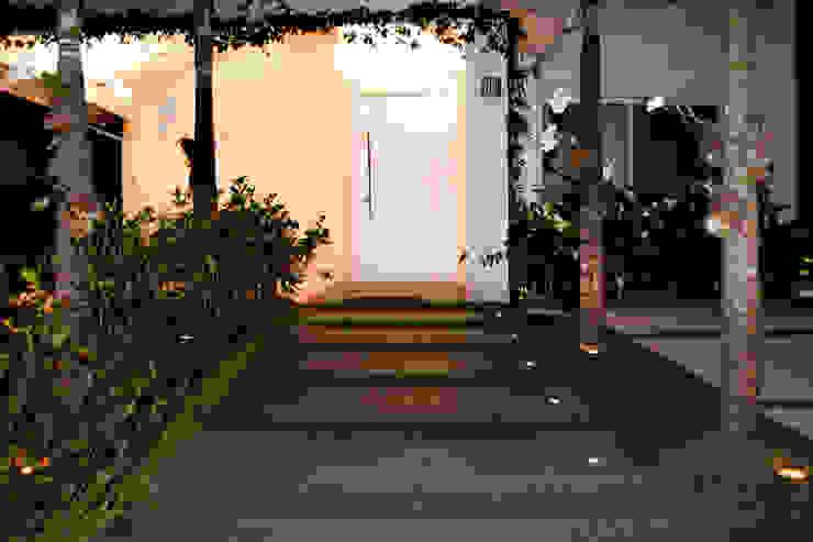 Entrada com deck em madeira por RAWI Arquitetura + Design Minimalista Madeira Efeito de madeira