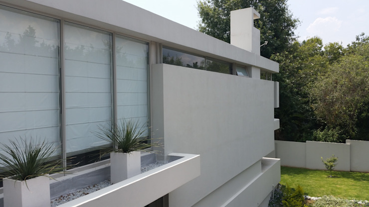 Detail view of the modern minimalist facade to the rear of the house. Floating wall panels and strip windows work to enforce the idea of independant vertical and horizontal planes Minimalist house by Green Evolution Architecture Minimalist Reinforced concrete