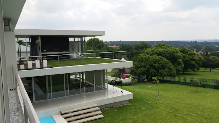 View from the master bedroom over the garden towards a magnificent view over the northern suburbs of Johannesburg. Horizontal floating planes supported by steel columns allowing full glass facades. by Green Evolution Architecture Minimalist Reinforced concrete