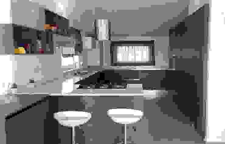 """Cucina a """"U"""" con colonne attrezzate, area lavaggio e cottura e penisola con snack di Meka Arredamenti Moderno"""
