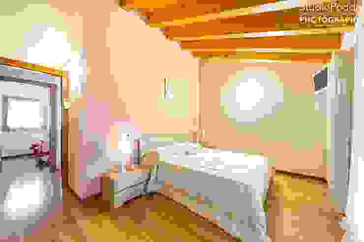camera matrimoniale con travi a vista Studio13podda Spazi commerciali moderni