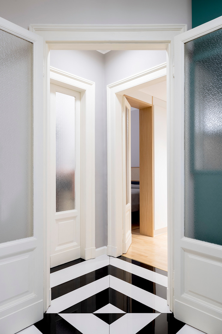 Il disimpegno triangolare verso la zona notte e il bagno, con porte recuperate Ingresso, Corridoio & Scale in stile eclettico di PLUS ULTRA studio Eclettico